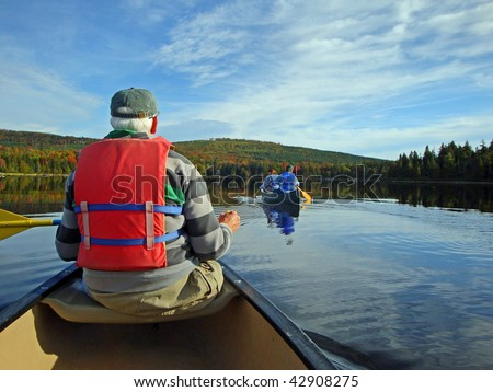 Senior man paddling a canoe with second canoe, calm waters and autumn colors in background.