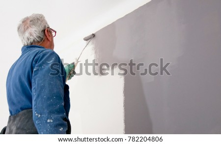Senior man painting grey wall. Home renovation concept