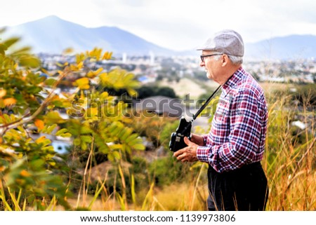 Senior man photographing natural landscape with old photographic camera #1139973806