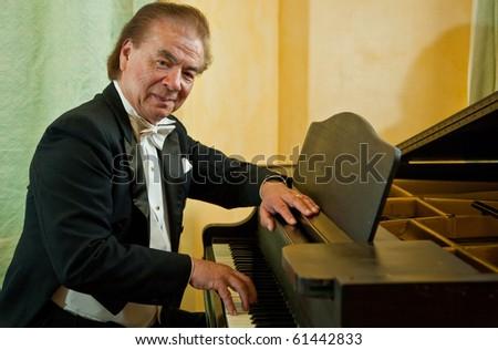 Senior man pianist playing on a grand piano. Nikolai Massenkoff, the star of the Massenkoff Russian Folk Festival.