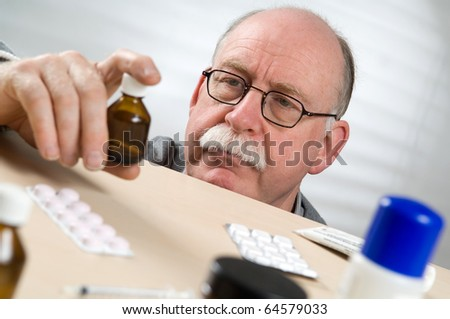 Senior man picking medicine bottle