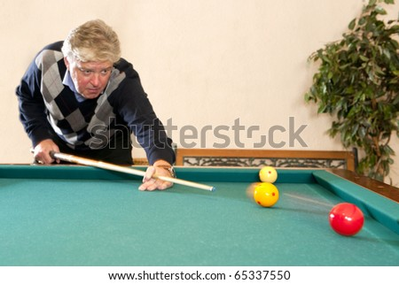 Senior man playing a game of carambole billiards - selective focus on the billiard balls