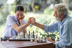 Senior man playing chess with young nurse. White male with asian woman. Hand shake.