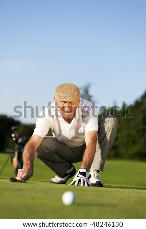 Senior man playing golf aiming for the hole, it is a wonderful clear summer late afternoon, the colors are very vivid