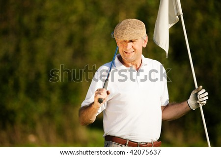 Senior man playing golf holding the flag in his hand