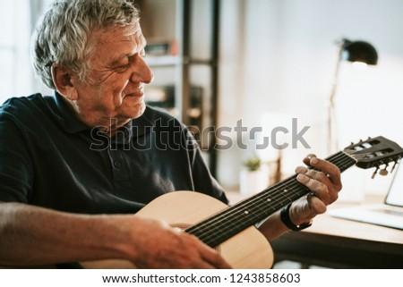 Senior man playing on his guitar