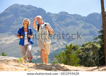 Senior man pointing the route of the hike to his wife as they walk