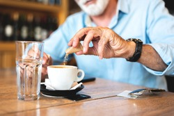 Senior man pouring sugar into coffee at restaurant