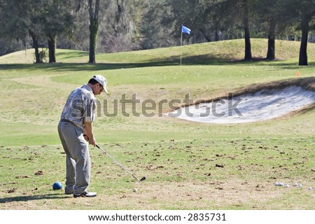 Senior man practicing golf game on the driving range.