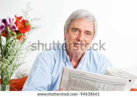 Senior man reading a newspaper in the living room