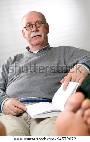 Senior man reading book while sitting on couch