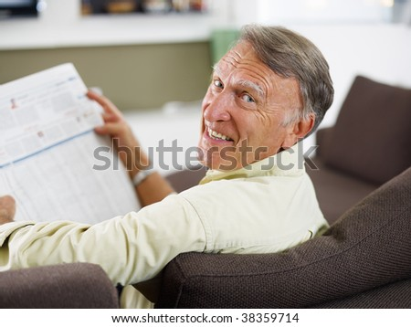 senior man reading newspaper at home and looking over shoulders