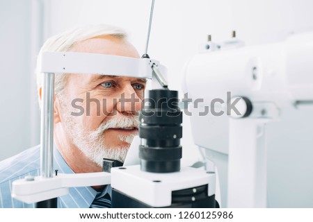 Senior man receiving eye exam at clinic, eyesight examination aged people #1260125986