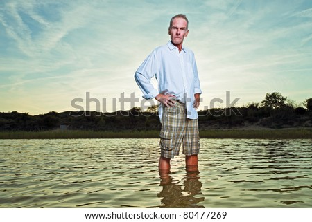 Senior man refreshing in water enjoying nature on hot summer day. Standing in pond.