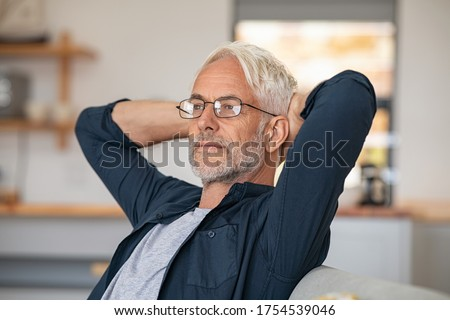 Senior man relaxing at home and thinking with hands behind head. Mature man wearing eyeglasses while resting at home and looking away. Retired old man sitting on couch, thinking about the future.