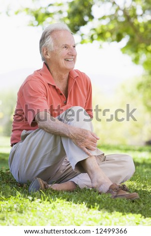 Senior man relaxing in countryside sitting on grass