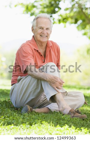 Senior man relaxing in park sitting on grass