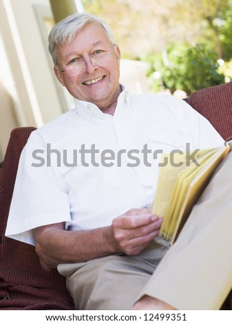 Senior man relaxing with book sitting on garden seat