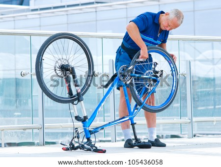 senior man repairing his bike