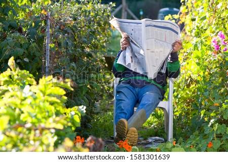 Senior man resting and having nap under newspaper in vegetable garden