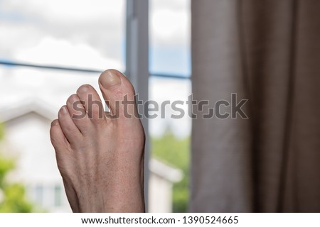 Senior man resting foot in house with window in the background to outside #1390524665