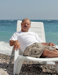 Senior man resting in the chaise lounge on a pebble beach against a turquoise  sea wearing in cotton shots and white  T-shirt