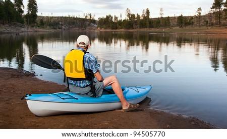 Senior Man Resting on Kayak Overlooking Rural Lake