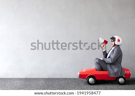 Senior man riding toy car. Full length portrait of funny businessman against concrete wall with copy space. Business start up concept Photo stock ©