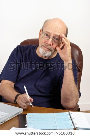 Senior man seated at desk with laptop computer and checkbook, worried about paying the bills.