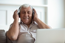 Senior man seated on sofa in living room hold laptop on lap wearing headphones listens favourite track having nostalgic mood enjoys songs of his youth, older generation using modern technology concept
