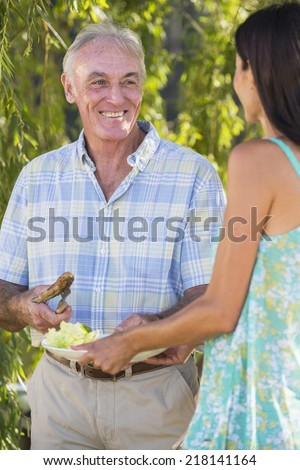 Senior Man Serving Food At Family Barbeque