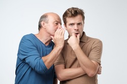 Senior man sharing secret or whispering gossips into his son ear, who is shocked and looking at camera with shocked expression on his face. Telling family secret concept