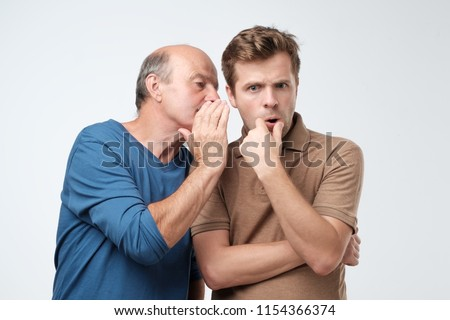 Senior man sharing secret or whispering gossips into his son ear, who is shocked and looking at camera with shocked expression on his face. Telling family secret concept Photo stock ©