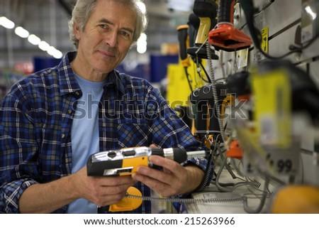 Senior man shopping for power drill in DIY shop, smiling, portrait #215263966