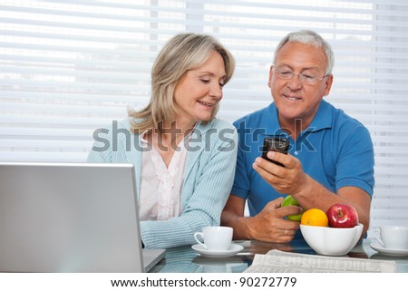 Senior man showing mobile phone to female