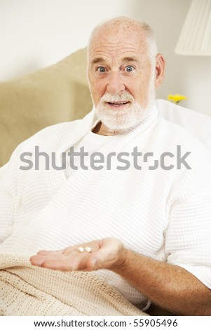 Senior man sick in bed doesn't want to take his medicine. - stock photo