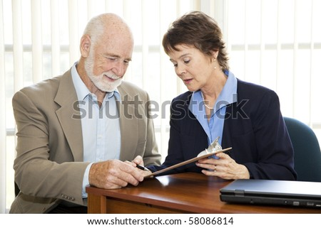 Senior man signing a contract in his attorney's office.