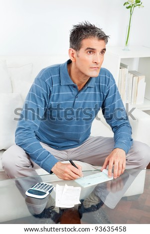 Senior man signing check on living room table - stock photo