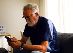 Senior man sitting alone in home and talking friend on smart phone.