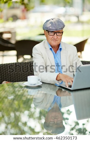 Senior man sitting at cafe and typing on laptop #462350173