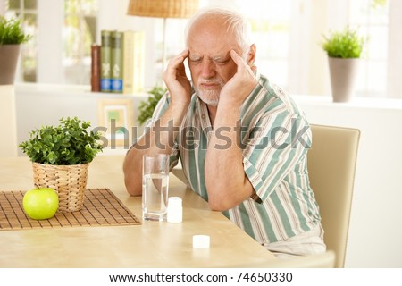 Senior man sitting at table, having bad headache, grimacing, taking medicine.?