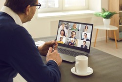 Senior man sitting at table having virtual group meeting with team of coworkers on laptop computer. Online business network communication, teamwork, home office workplace, hybrid work schedule concept