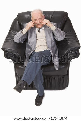 Senior man sitting in an armchair and putting on his glasses.