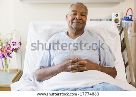 Senior Man Sitting In Hospital Bed