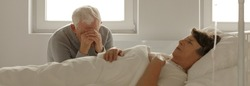 Senior man sitting next to his dying wife's hospital bed and crying