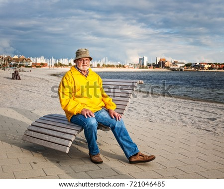 Senior man sitting on bench, relaxing on the beach. Vacation background. Baltic sea coast, Germany, travel destination  #721046485
