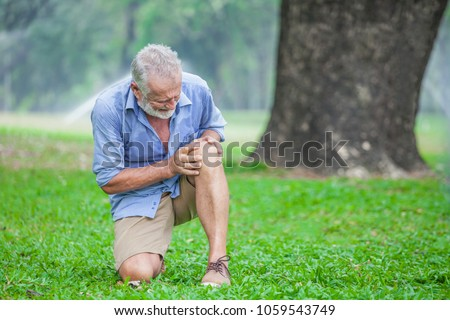 Senior man sitting or flop falling  in autumn park and having knee pain. kneel Arthritis pain concept.