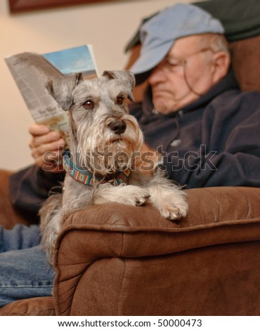 Senior man sitting, reading and relaxing with his best friend, a dog. - stock photo