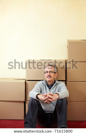 Senior man sitting relaxed in front of moving boxes