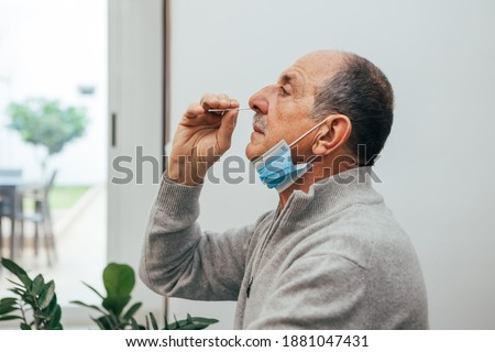 Senior man sitting, self test for COVID-19 at home with Antigen test kit. Coronavirus nasal swab test for infection. Medicine and health-related services online.